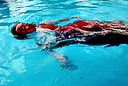 Woman with red mask floats in a pool
