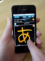 Student learning to write Japanese characters using app on an Apple iphone 4G smart phone