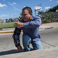 """Geovanny Sierra, journalist with UNETV<br /> <br /> """"On 26 November at around 4pm, I began to give live coverage of some protests against the government. The incident occurred at 6:35pm. <br /> <br /> I felt the hit of the bullet, I felt that it went into the bones, but I also felt them go numb, like they went to sleep, a bit like the funny bone in your elbow. I thought that it was just a broken bone, with a bit of rest, I'd soon be back at work.<br /> <br /> I was transmitting live. I wanted my family to know that I was okay. But then someone else else was saying that I'd been hit in the stomach.<br /> <br /> We were around the edge of a commercial centre, a mall, I hid down behind a steep curb, I thought I'd be protected there. But I was hit. The protestors took me to the hospital.<br /> <br /> The bullets came from a bus. COFADEH have testimonies that bullets were shot from the same bus against a protest on the day before.<br /> <br /> The official version of events is that the bus was being used by prison guards, going from the La Granja courts taking three prisoners accused of extortion, to prison. And they allege that the bus was attacked with the intention of liberating the prisoners, so they opened fire.  In first place, the route they would have taken for that journey is a different one, they would have had to take a very different route, breaking all their protocols, and going into an area where there was known to be a protest. The videos show that the bus was not attacked in any way.<br /> <br /> The videos show that there was nothing between me and the bus, and the shots were not what are called persuasive shots, over my head, but directly at me. <br /> <br /> From 2001 until now, 67 journalists, people working for communication, have been killed. But only three have been taken to justice. For most of them there is no process of investigation, the people who have killed our colleagues enjoy complete impunity."""""""
