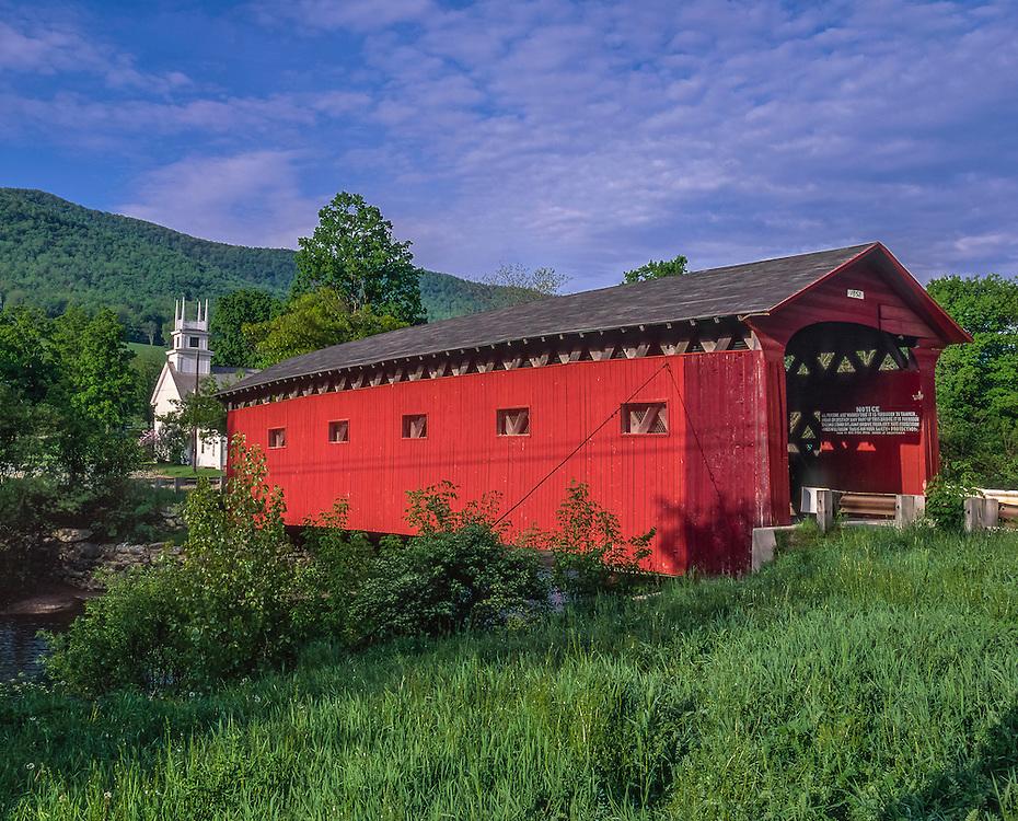 West Arlington Covered Bridge over Battenkill River, summer, church beyond.  West Arlington, VT