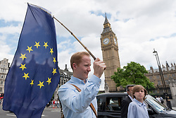 © Licensed to London News Pictures. 24/06/2016. London, UK. A man carries a European Union flag in front of the Houses of Parliament, on the day that Britain voted to leave the European Union. Photo credit : Stephen Chung/LNP
