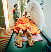 A young girl has ayurvedic treatment while her mother looks on. Kerala, India.
