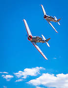 """AT-6 """"Baby Boomer"""", flown by Fred Telling of Port Orange, Florida and an AT6-B """"Baron's Revenge"""", flown by Chris Rushing of San Clemente, California.  T-6 Gold Race, Sunday at Reno."""