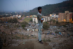 A young man stands in Ashok Nagar, a slum neighborhood that is far from the city center.  It can be very difficult and costly for TB patients who live in the far away slums to get to a health clinic to receive their daily medicines.  Transportation to a clinic may only cost twenty cents a day, but that can represent nearly 10% of a patient's salary.  Some patients will simply stop going to the health clinics in order to save the transportation money, or in order to not miss work.