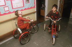 Young children with learning disabilities riding tricycles in school corridor,