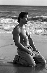 shirtless muscular man kneeling by the ocean
