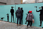 Prague citizens peer through peep holes without realising that behind the hoarding is merely a construction site, on 18th March, 2018, in Prague, the Czech Republic.