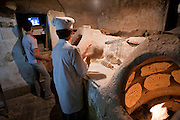 Bakers watch TV while working at a bakery in the city of Yazd, Iran.