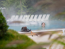 Woman hiker relaxing in swimming pool of Paracelsus-Therme, Bad Liebenzell, Baden-Württemberg, Germany