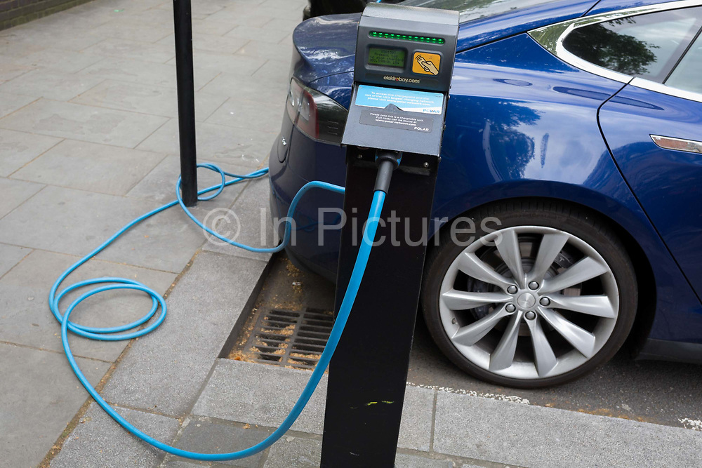 A blue Tesla Model S car recharges its batteries from a street recharging point provided by pay-to-use Polar Network from an Elektrobay charge point in St. Jamess Square, on 29th April 2019, in London, England.