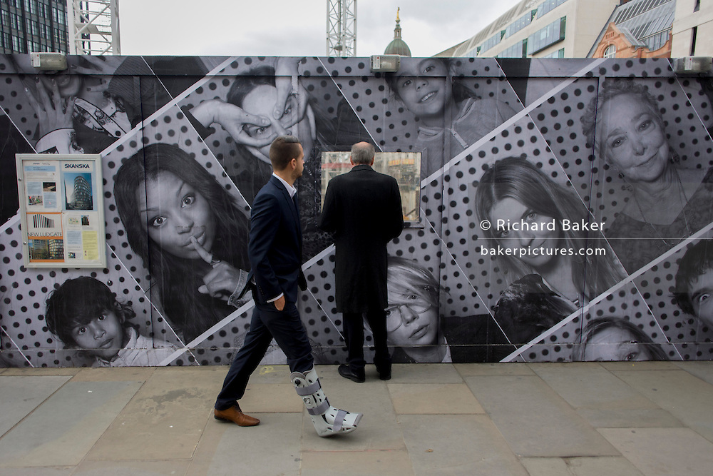 As a businessman walks past wearing a leg brace, a curious man looks through the aperture of a construction site window with a hoarding of many faces.