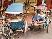 02 FEBRUARY 2013 - PHNOM PENH, CAMBODIA:  A tri-shaw driver sleeps while he waits for customers in a market in Phnom Penh, Cambodia.     PHOTO BY JACK KURTZ