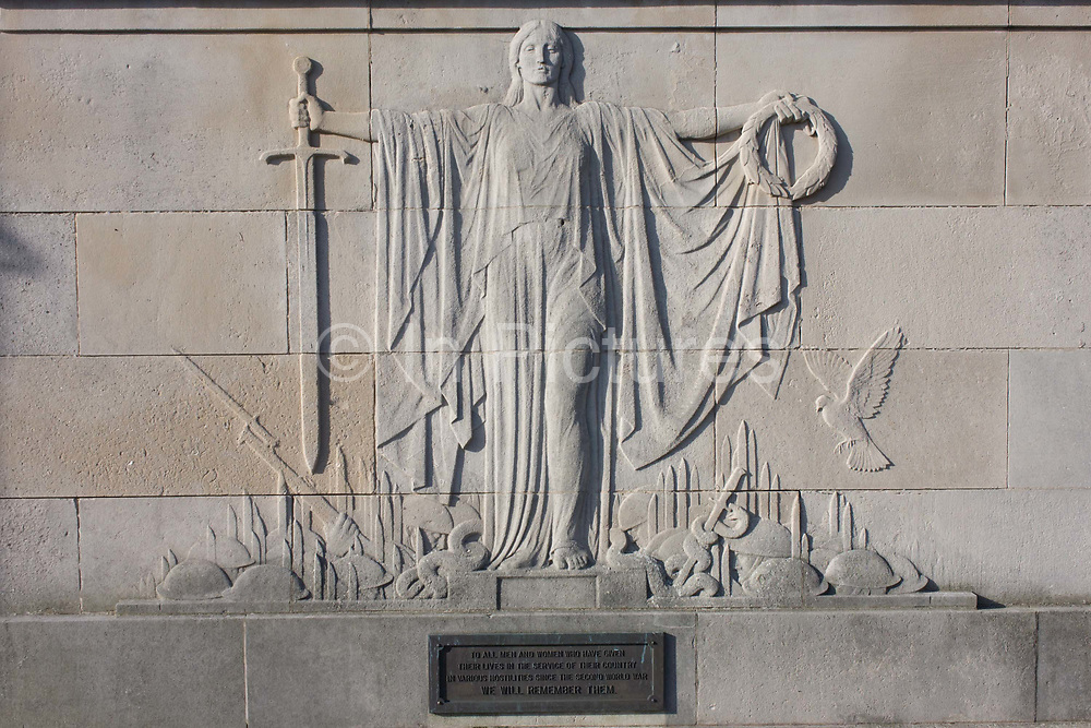 Detail of a side relief of the war memorial in Prospect Square, Harrogate, North Yorkshire, England. Looking in detail at the cenotaph we see the sword of sacrifice with a wreath and a dove of peace. This huge Cenotaph is situated in the centre of Harrogate, near St. Peter's Church. Listed are the names of those who perished in WWI and WWII. The front brass plaque is made up of 3 panels, each consisting of 3 columns, with the names of 641 people who perished in WWI, the list continuing on the rear plaque. The rear plaque is in the same format as the front, with the remaining 238 names from WWI. Also included on the lower half are the names of 314 people who died in WWII. Designed by architects Prestwich & Sons, the two relief panels sculpted by Gilbert Ledward.