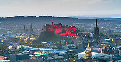 View of  Edinburgh Castle illuminated in red  in the evening from Salisbury Crags in Edinburgh, Scotland, United Kingdom.