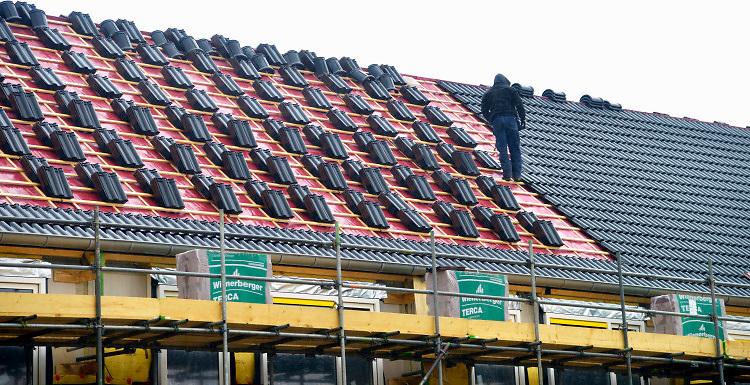 Nederland, Nijmegen, 8-1-2019Bouwvakkers werken aan een nieuwbouwproject. Dakdekker,dakpannen.Foto: Flip Franssen
