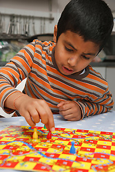 Asian boy playing snakes and ladders game