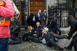 London, UK. 10 June, 2019. Security guards fail to prevent activists from BP or not BP? blocking access to the National Portrait Gallery in protest against BP's sponsorship of the BP Portrait Award. The energy company has sponsored the National Portrait Gallery's award for 30 years, but its high-profile involvement is attracting widespread criticism due to the intensifying focus on environmental issues. A number of artists, including previous award winners such as Wim Heldens and Craig Wiley, have called on the gallery to end its sponsorship by BP.
