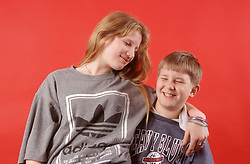 Portrait of brother and sister hugging and laughing,