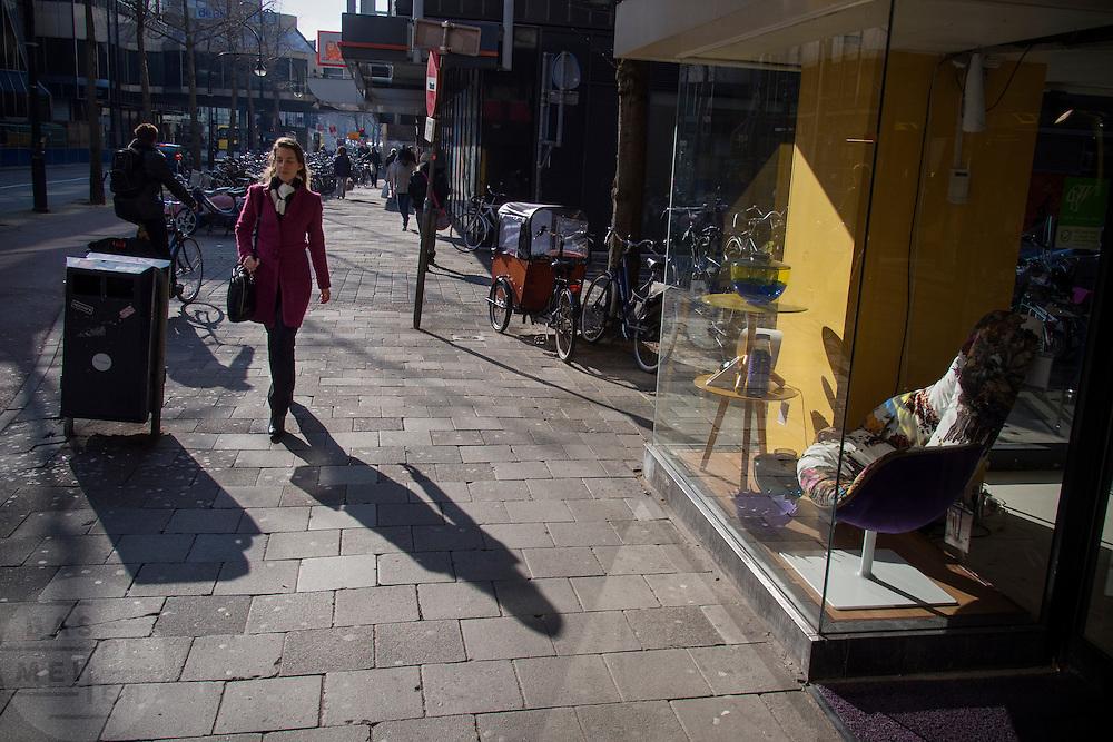 In Utrecht loopt een vrouw in zonlicht langs een meubelwinkel in de binnenstad.<br /> <br /> In Utrecht a woman passes a furniture shop in the city center.