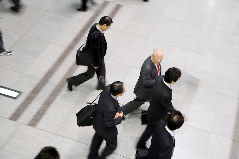 overhead view of group of businessmen walking in one direction Japan Tokyo