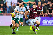 Alex Gogic (#13) of Hibernian FC and Ben Woodburn (#9) of Heart of Midlothian FC tussle for the ball during the Cinch SPFL Premiership match between Heart of Midlothian and Hibernian at Tynecastle Park, Edinburgh, Scotland on 12 September 2021.