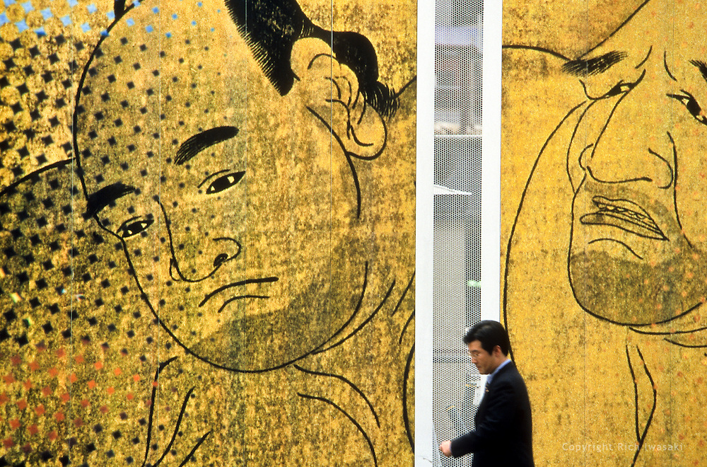 Pedestrian passes beneath large wall graphics at construction site in Roppongi district of Tokyo, Japan