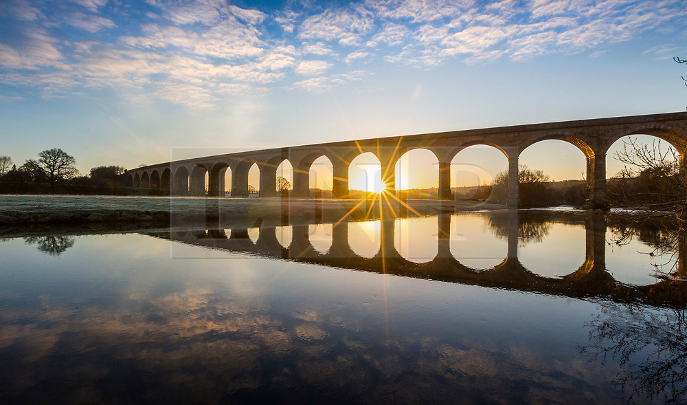 © Licensed to London News Pictures. 01/02/2021. Arthington UK. The sun rises this morning between one of the 21 arches that make up Arthington viaduct near Otley in Yorkshire. Photo credit: Andrew McCaren/LNP