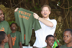 Prince Harry poses with a t-shirt on stage during a visit to 'Nature Fun Ranch', which allows young people to speak freely with one another about important topics, including HIV/AIDS, providing them with a positive focus to guide their lives in the right direction, during his tour of the Caribbean.