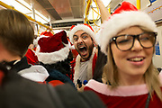 People dressed up as Santas on an underground train. There were hundreds of people on this train, all having fun on their way to a Santa run in London, UK.