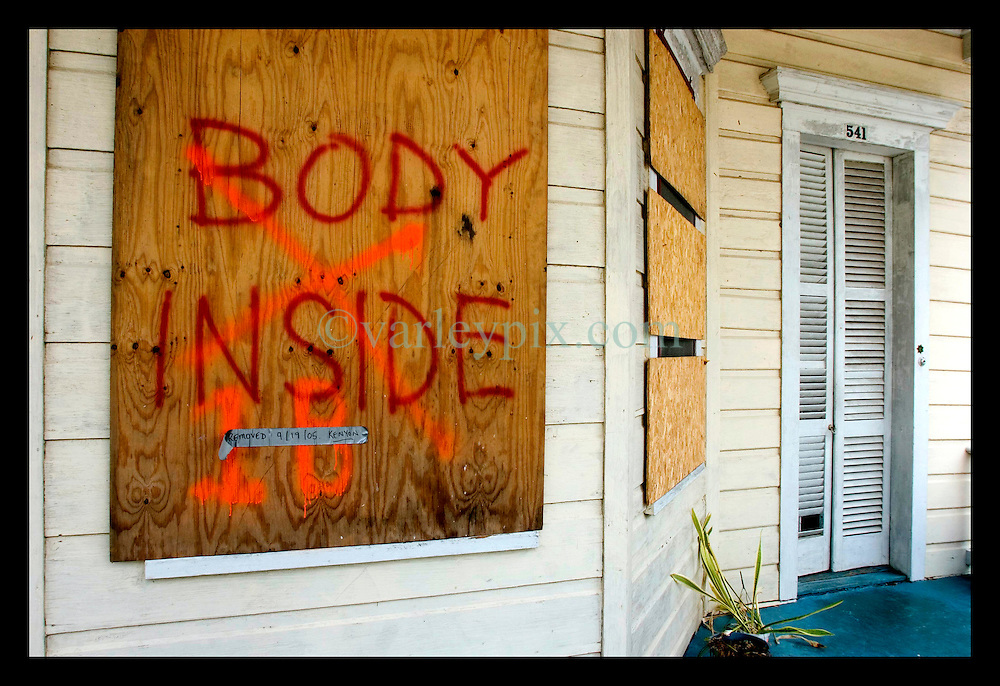 7th Oct, 2005. Hurricane Katrina aftermath, New Orleans, Louisiana. 'Body Inside.' The stark spray paint on the outside of a house in Uptown New Orleans. A tape attached to the panel reads 'Removed 9.19.05 Kenyon.' Kenyon are the private contractors hired by the city to pick up corpses left behind after the storm.