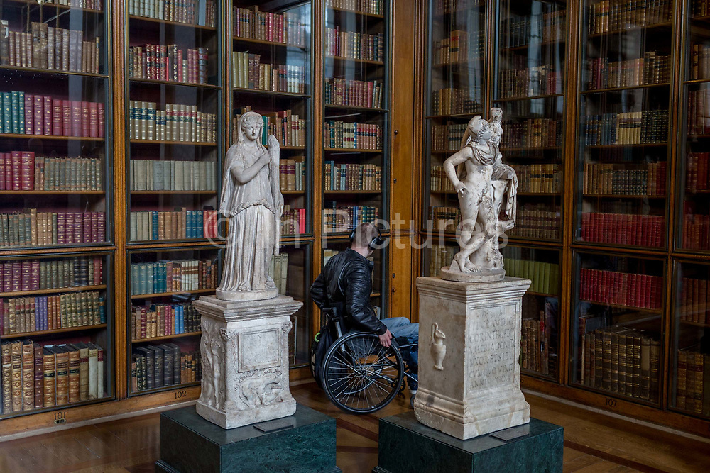 A wheelchair user moves between 2nd century Roman copies from Greek originals of Demeter holding a torch L and Gannymede with the eagle of Zeus R, in the Enlightenment Gallery of the British Museum, on 11th April 2018, in London, England.