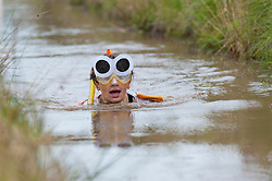 © Licensed to London News Pictures. 30/08/2015. Llanwrtyd Wells, Powys, Wales, UK. Jade dresses as a goldfish for the event. World Bogsnorkelling Championships, conceived 30 years ago in a Welsh pub by landlord Gordon Green, are held every August Bank Holiday at Waen Rhydd Bog. Using unconventional swimming strokes, participants swim two lengths of a 55 metre trench cut through a peat bog wearing snorkel and flippers. The world record was broken in 2014 by 33 year old Kirsty Johnson from Lightwater, Surrey, in a time of 1 min 22.56 secs. Photo credit: Graham M. Lawrence/LNP