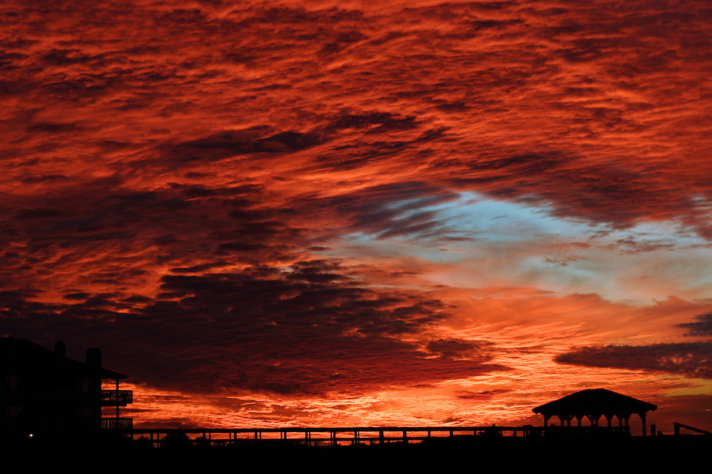 A fiery-red sunset takes place over a gazebo near a marsh at Wrightsville Beach, NC.