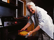 Madeleine Kamman removing Blue Cheese Quiche from oven in the kitchen of Kirsten and Carl Dixon's Winterlake Lodge, Alaska.  (Model Released)