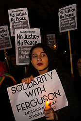 London, November 26th 2014. A vigil for teenager Mike Brown who was shot dead by a policeman in Ferguson, Missouri this year, takes place outside the US embassy in London. Anti-racism and human rights campaigners called the 'emergency' protest following a court verdict that clears Police Officer Darren Wilson of murder. PICTURED: An anti-racism protester holds a candle as protesters remember the late Mike Brown, gunned down by police in Fergusson, Mussouri.