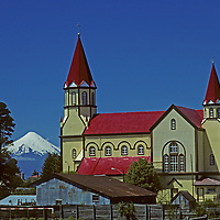 CHILE, Lakes District. Village cathedral in Puerto Varas. Volcan Osorno bkg.