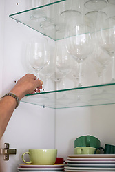 Close-up of a woman taking wineglass from cupboard, Munich, Bavaria, Germany