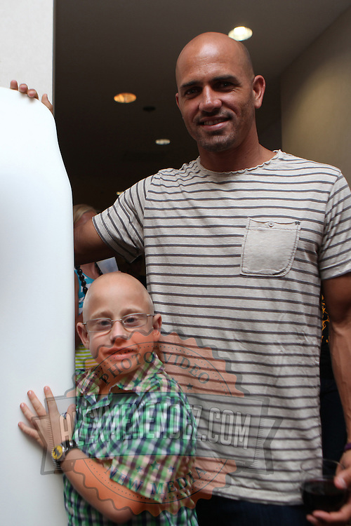 """Blake, a young kidney recipient, poses with ASP World Champion Kelly Slater at the """"Taste of Brevard"""" dinner and auction on day two of the 28th annual National Kidney Foundation, Rich Salick Pro/Am surf festival on Friday, September 1, 2013 in Cocoa Beach, Florida. This event raises thousands of dollars for people with kidney disease and also benefits the services of the NKF of Florida. (AP Photo/Alex Menendez)"""