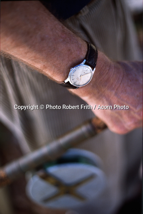 Man's arm holding a vintage fishing rod and old wrist watch