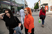 Woman with dyed orange hair and matching shirt in Birmingham, United Kingdom.