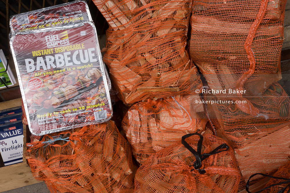 Disposable BBQ and bags of kindkling wood in bags on sale in small north Devon village corner shop.