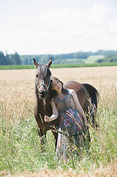 Mature woman standing with her brown horse on wheat field and smiling, Bavaria, Germany