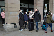 On the day that Chancellor of the Exchequer Rishi Sunak unveiled a £30bn package to boost the economy and get the country through the coronavirus outbreak, an Asian group of visitors wearing face masks look up at Big Ben as other tourists walk past with their baggage in Westminster, on 11th March 2020, in London, England.
