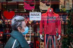 © Licensed to London News Pictures. 17/12/2020. LONDON, UK.  A shopper passes a window display selling facemasks in Oxford Street as the capital experiences Tier 3, Very High Alert Level, restrictions as the coronavirus pandemic continues.  Photo credit: Stephen Chung/LNP