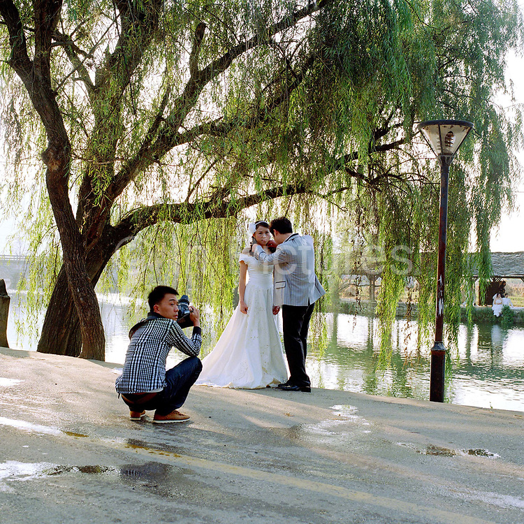 A Han Chinese couple  from Guiyang have their wedding photographs taken in the Buyi ethnic minority village of Shi Tou Zhai. It is common for Han couples to wear western style wedding dresses and travel to the countryside around the city for their wedding photographs.