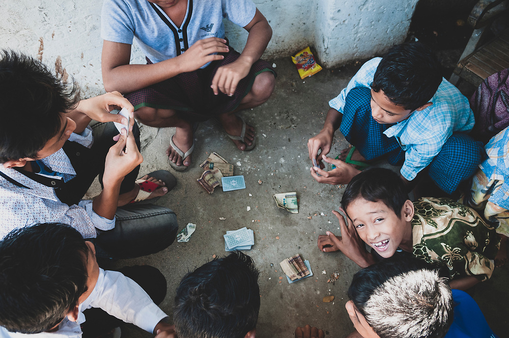 Mandalay, Myanmar - November 10, 2011: A group of boys play a game of cards and gamble in Mandalay.
