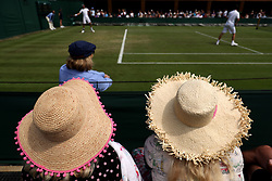 Spectators wear straw hats as they watch the action on day four of the Wimbledon Championships at the All England Lawn Tennis and Croquet Club, Wimbledon
