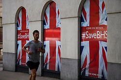 """© Licensed to London News Pictures. 10/06/2016. London, UK. A man runs past signs reading """"COME ON BRITAIN #Save BHS in the window of British Homes Stores (BHS) Headquarters in central London. British department store BHS is due to be liquidated after a buyer for the company failed to materialise. Photo credit: Ben Cawthra/LNP"""