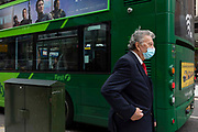 An man wearing a suit and tie and a blue surgical face mask to prevent the spread of Covid-19 passes by a green bus on 18th August, 2021 in Leeds, United Kingdom. The UKs Office for National Statistics ONS has announced the number of coronavirus-related deaths in England and Wales is the highest since March.