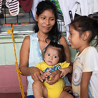 Inside a school building, Lilian Leticia Garcia Sanchez looks after her children Estiven Saul and Angie Julibeth. The school has been turned into a temporary shelter for people flooded out by Eta and Iota in San Pedro Sula.